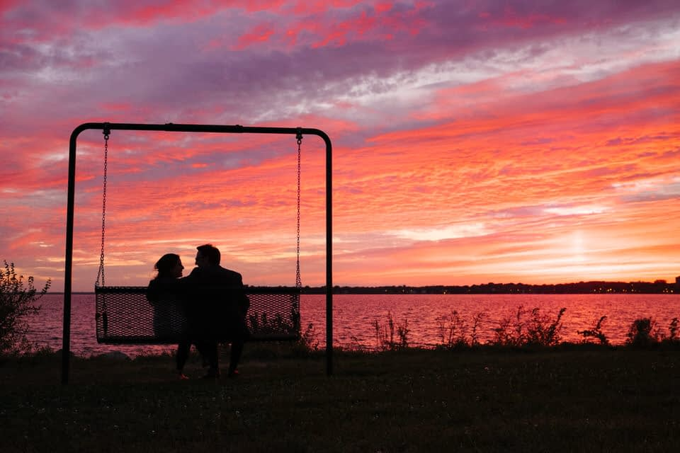 Happy newly engaged couple after sunset proposal near saint lawrence river