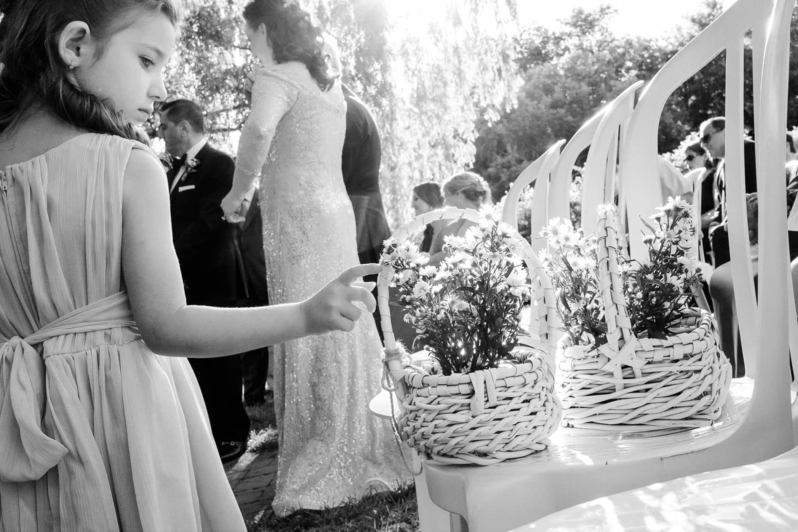 Flower girl curiously touching a flower basket