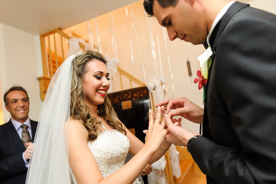 Groom putting ring on bride at her parents' house
