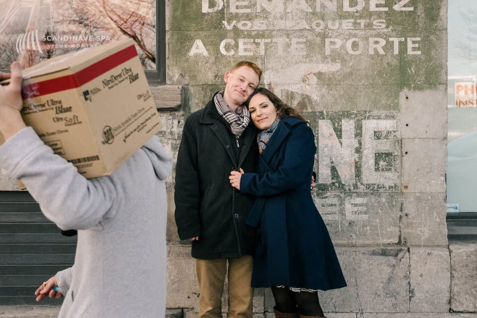 Engagement photo with man walking by