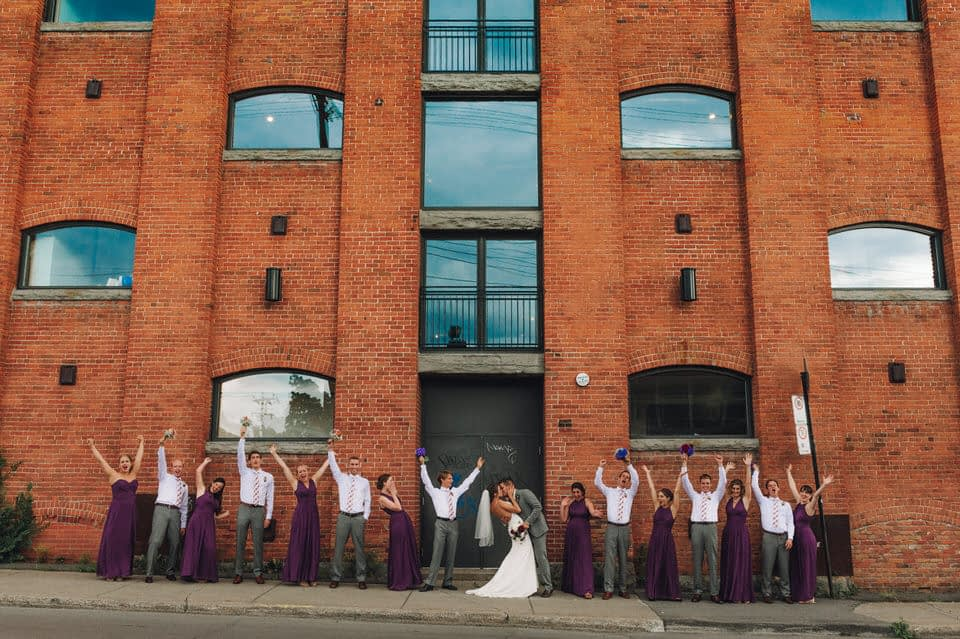 The entire wedding party standing in front of a tall building and cheering