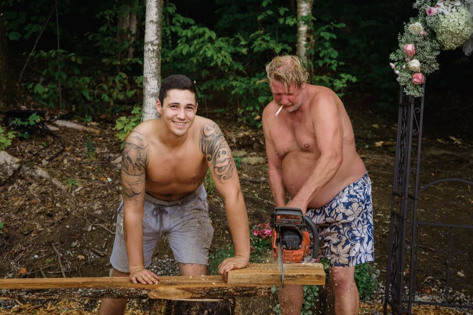 Groom and father of the bride using a chainsaw to build log benches