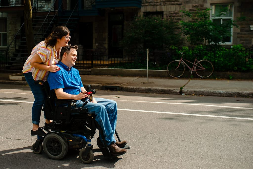 Photo of woman riding on the back of her fiancé's wheelchair as he rolls down the street