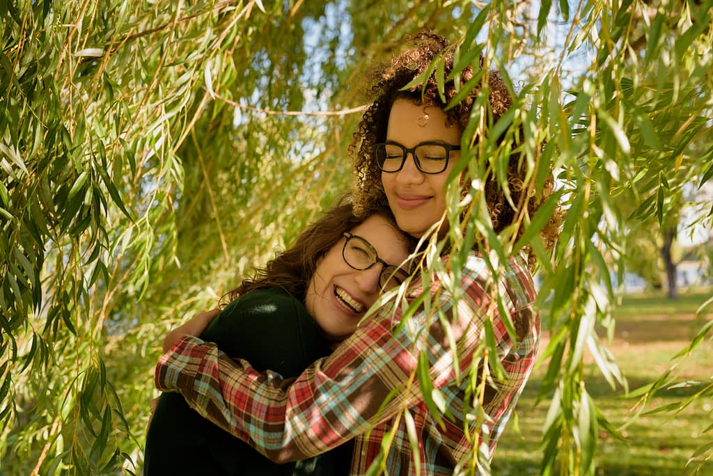 Two women hugging under willow leaves