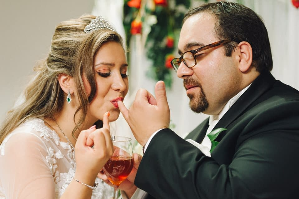 Groom and bride feed each other honey to symbolize sweetness of life