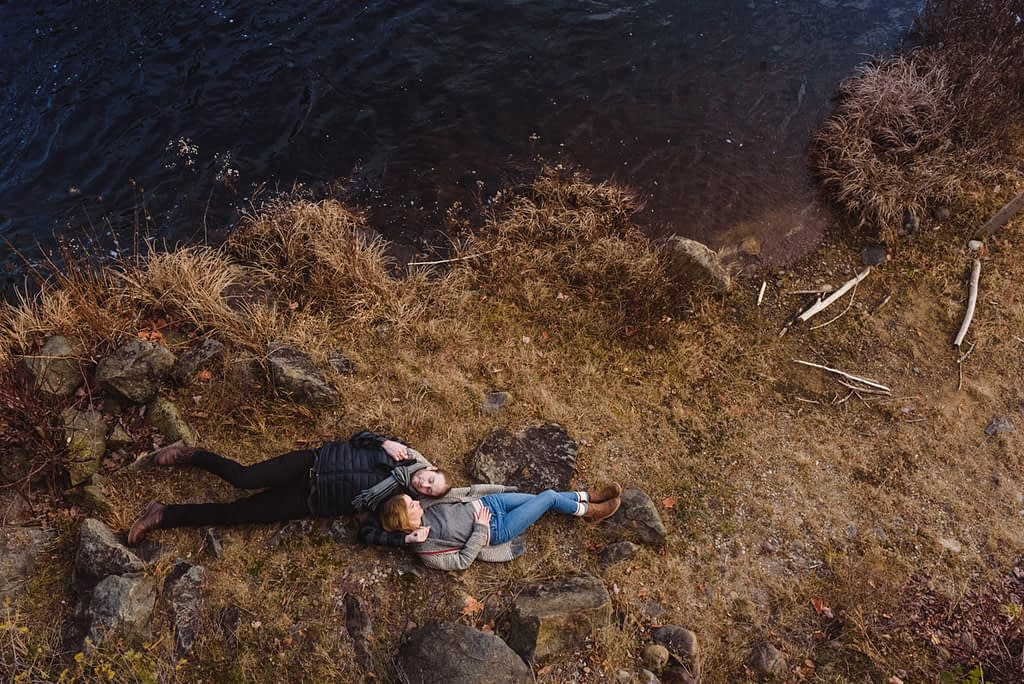 engagment couple lying grass river quebec