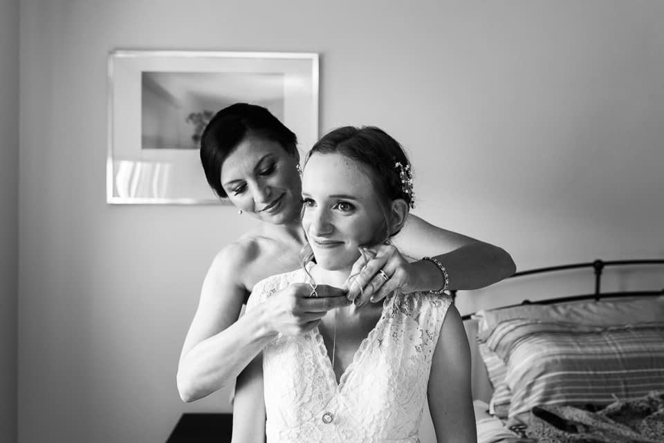Friend putting necklace on bride