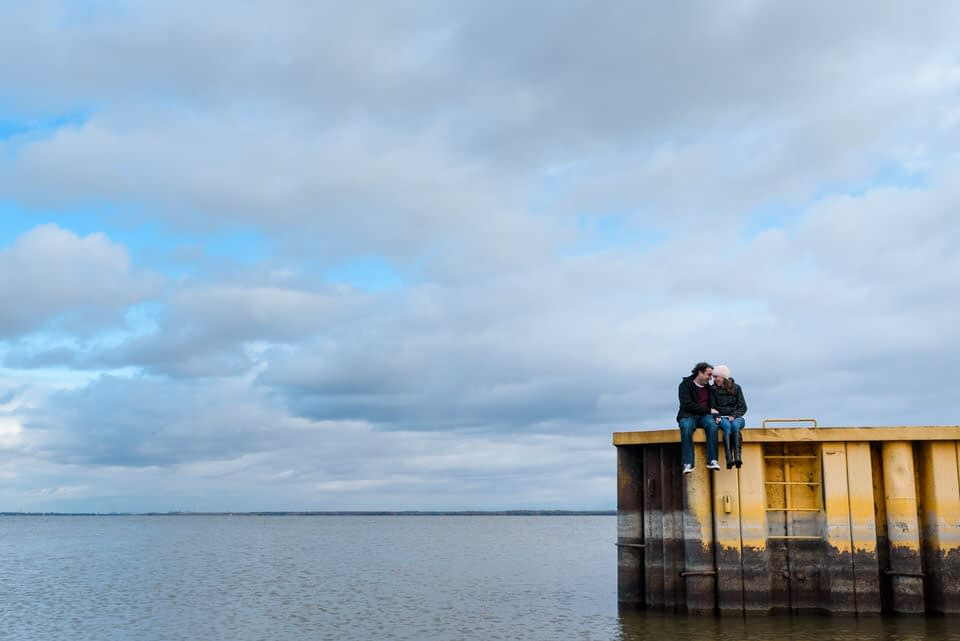 Guy kissing girl on forehead sitting on a dock at Pointe-Claire