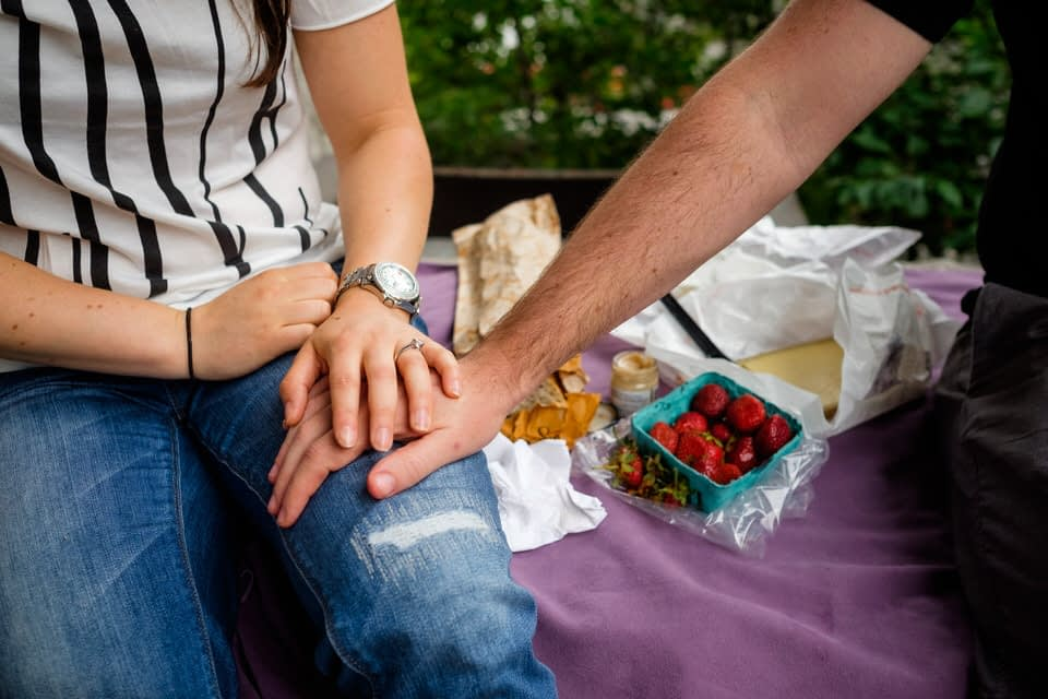 Couple enjoying a romantic picnic with wine and cheese and strawberries
