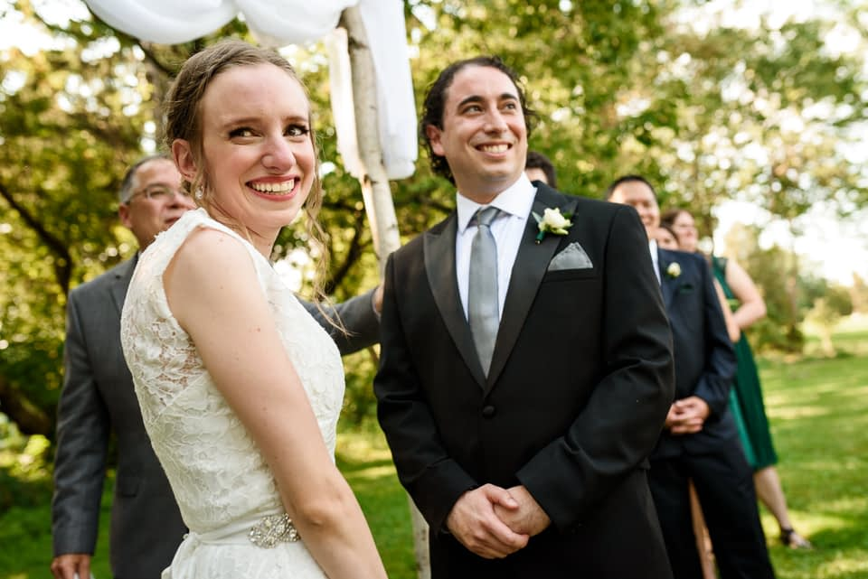 Bride and groom smiling at their guests during wedding ceremony outdoors