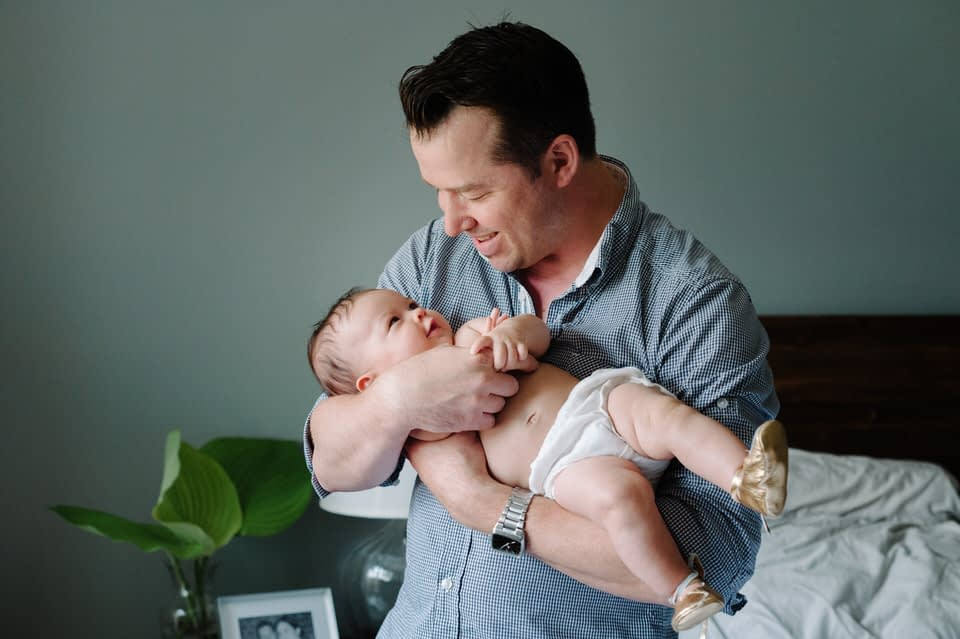 New father holding baby in family photo session