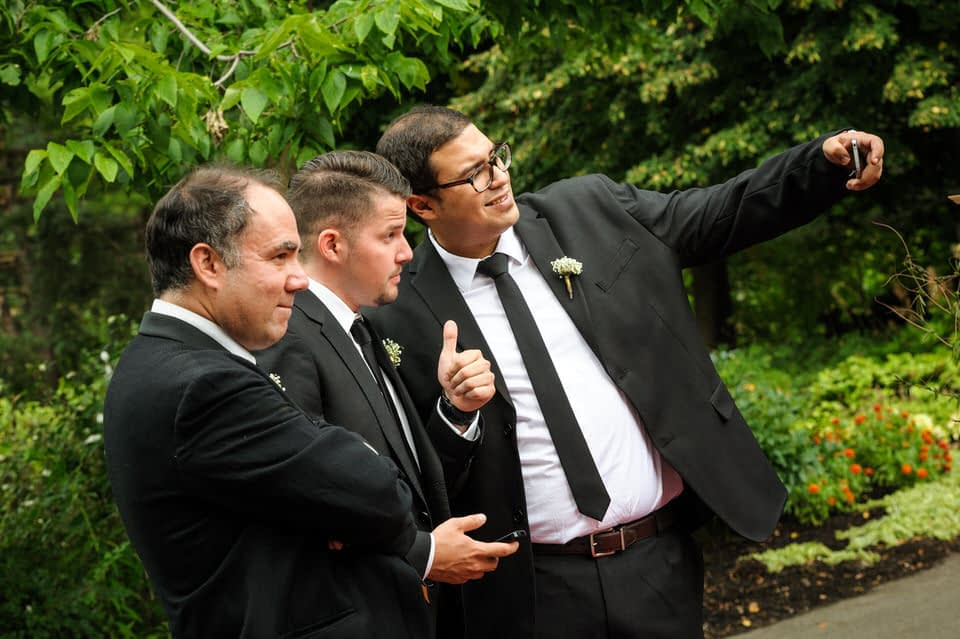 Groomsmen taking selfies at wedding at Parc Jean-Drapeau