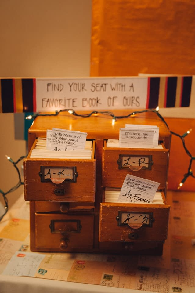 Library-theme wedding place cards so guests can find their seat with a book