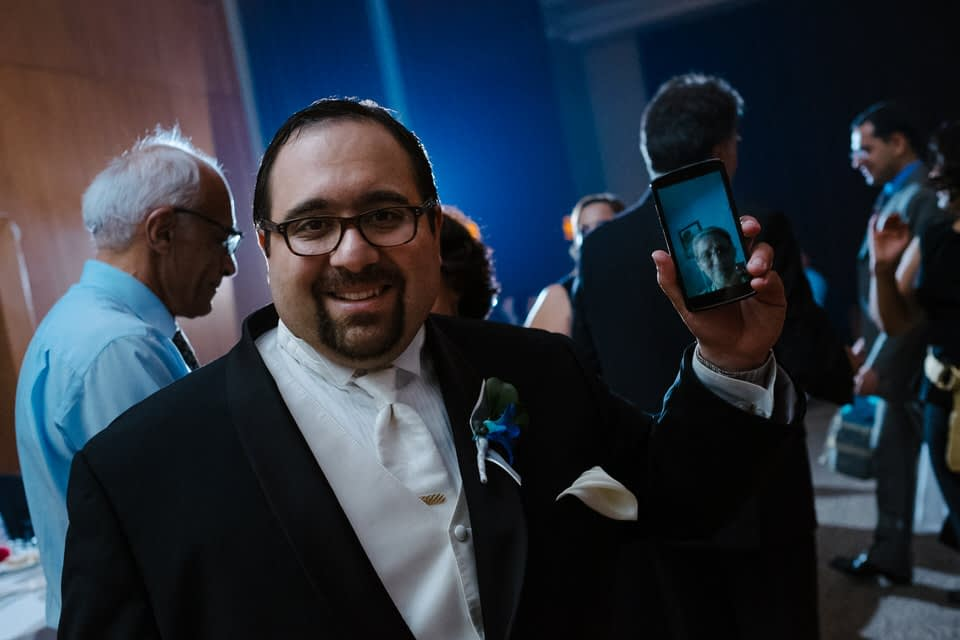 Groom skyping with a relative during wedding