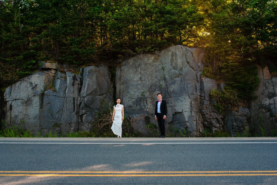Wedding portrait in front of a craggy rock face near a country highway
