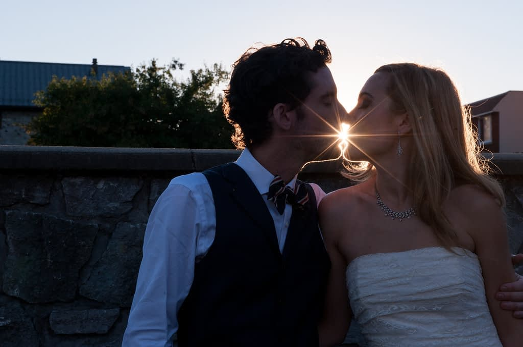 Silhouette of bride and groom kissing at sunset with sun flare