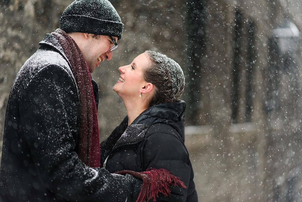 Wedding couple smiling in the snow flakes