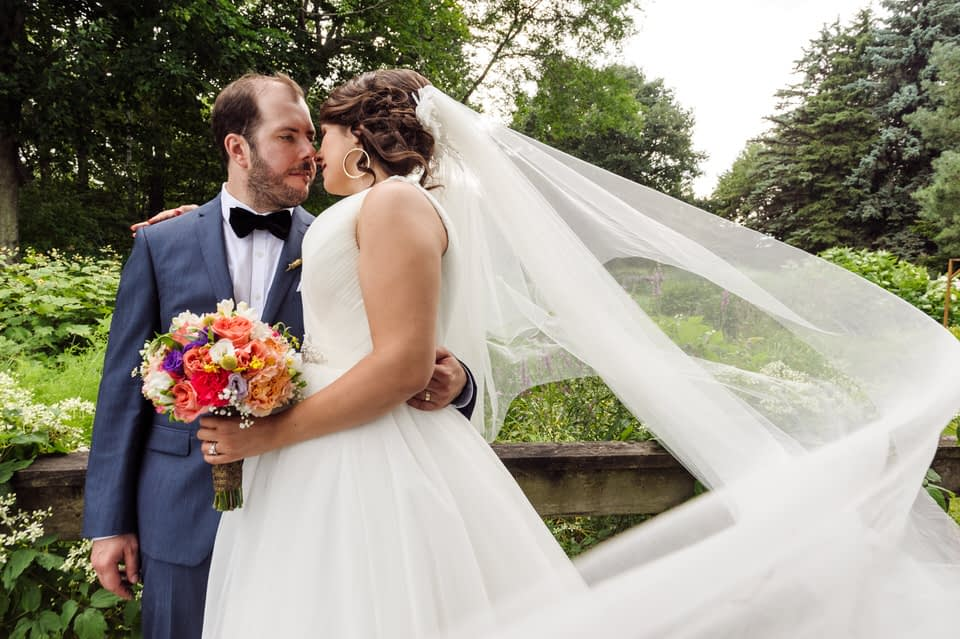 Wedding portrait of bride and groom with long veil at Parc Jean-Drapeau