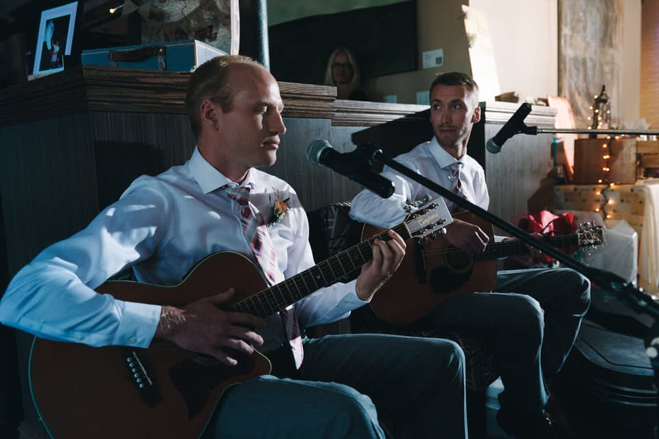 Groomsmen playing a song at the wedding reception