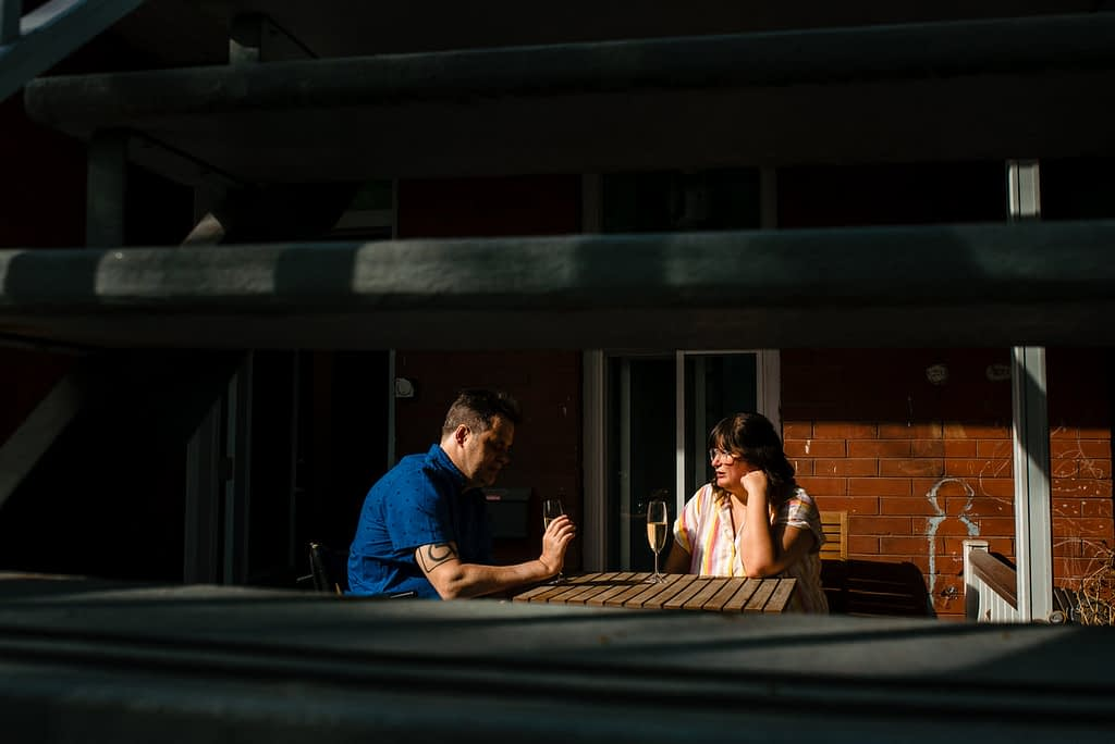 Engaged couple chatting in the sunset on their porch