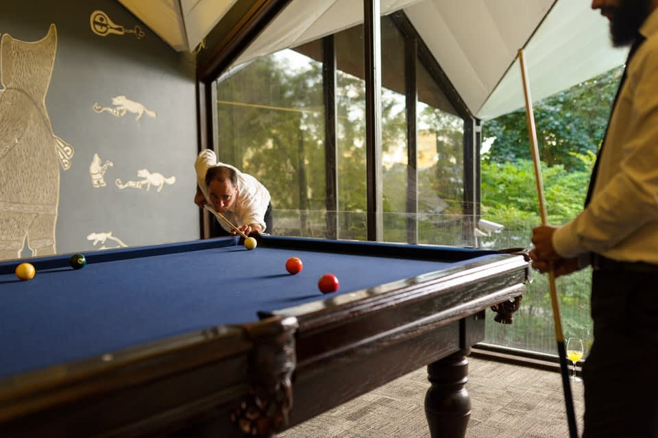 Wedding guest playing pool at La Toundra wedding venue