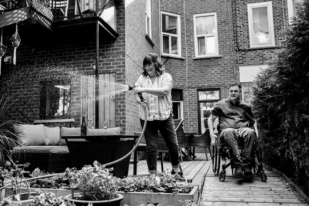 Woman waters flowers in backyard garden while man heads down wheelchair ramp