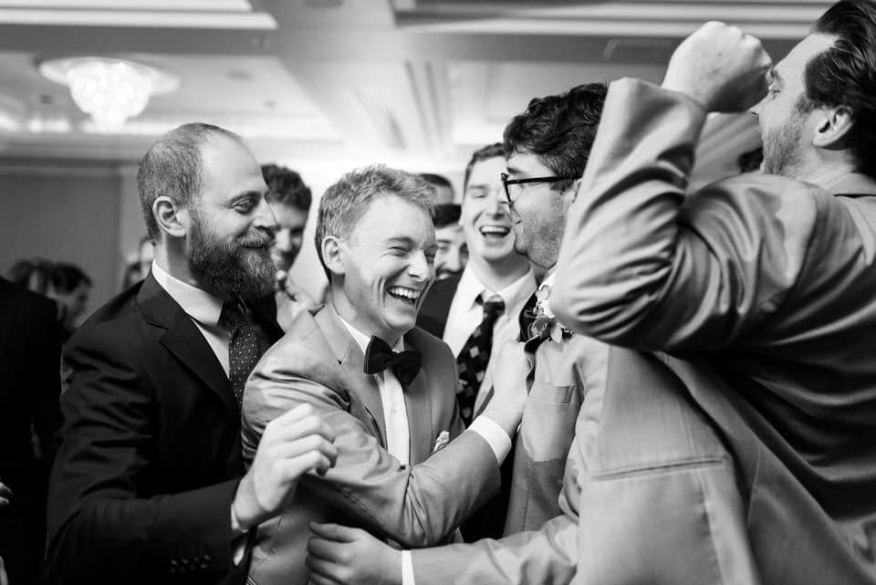 Happy groom surrounded by friends