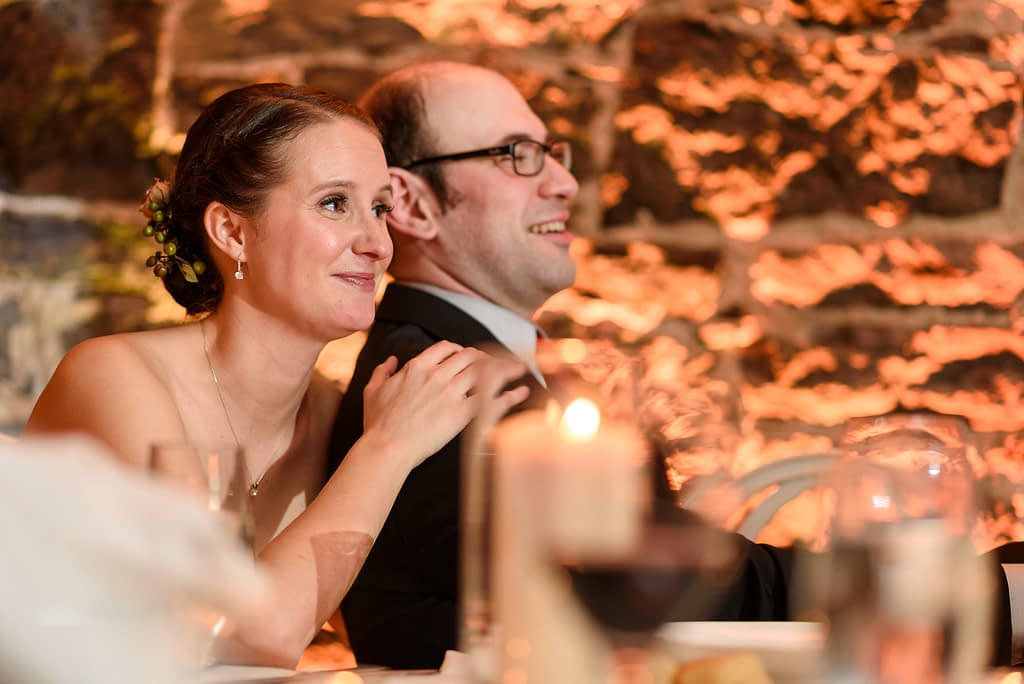 Bride leaning on groom and listening to touching speech