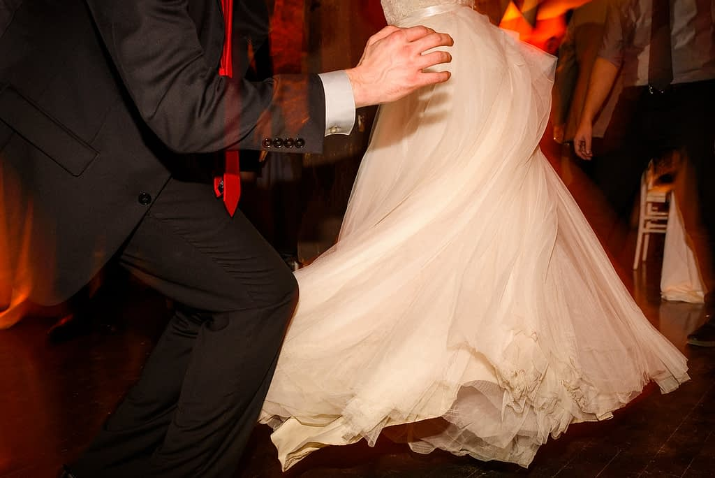 Close of up bride's wedding dress spinning as they dance together