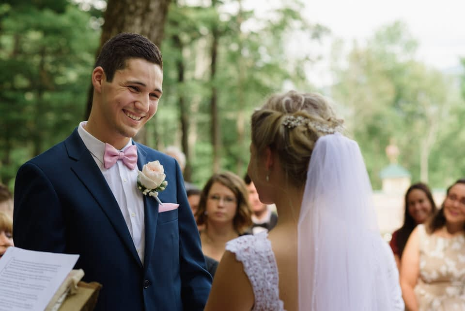 Groom smiling down at bride during wedding ceremony