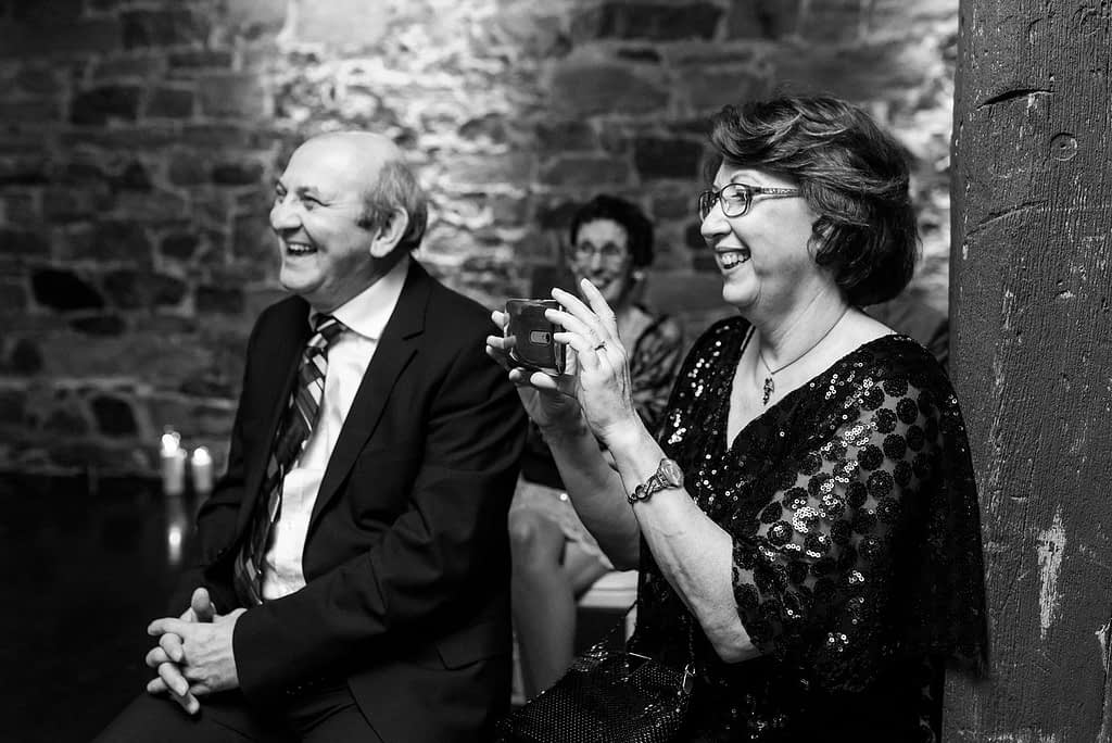 Groom's parents laughing and taking a photo during the ceremony
