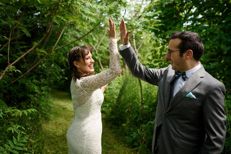 Wedding couple high fiving each other