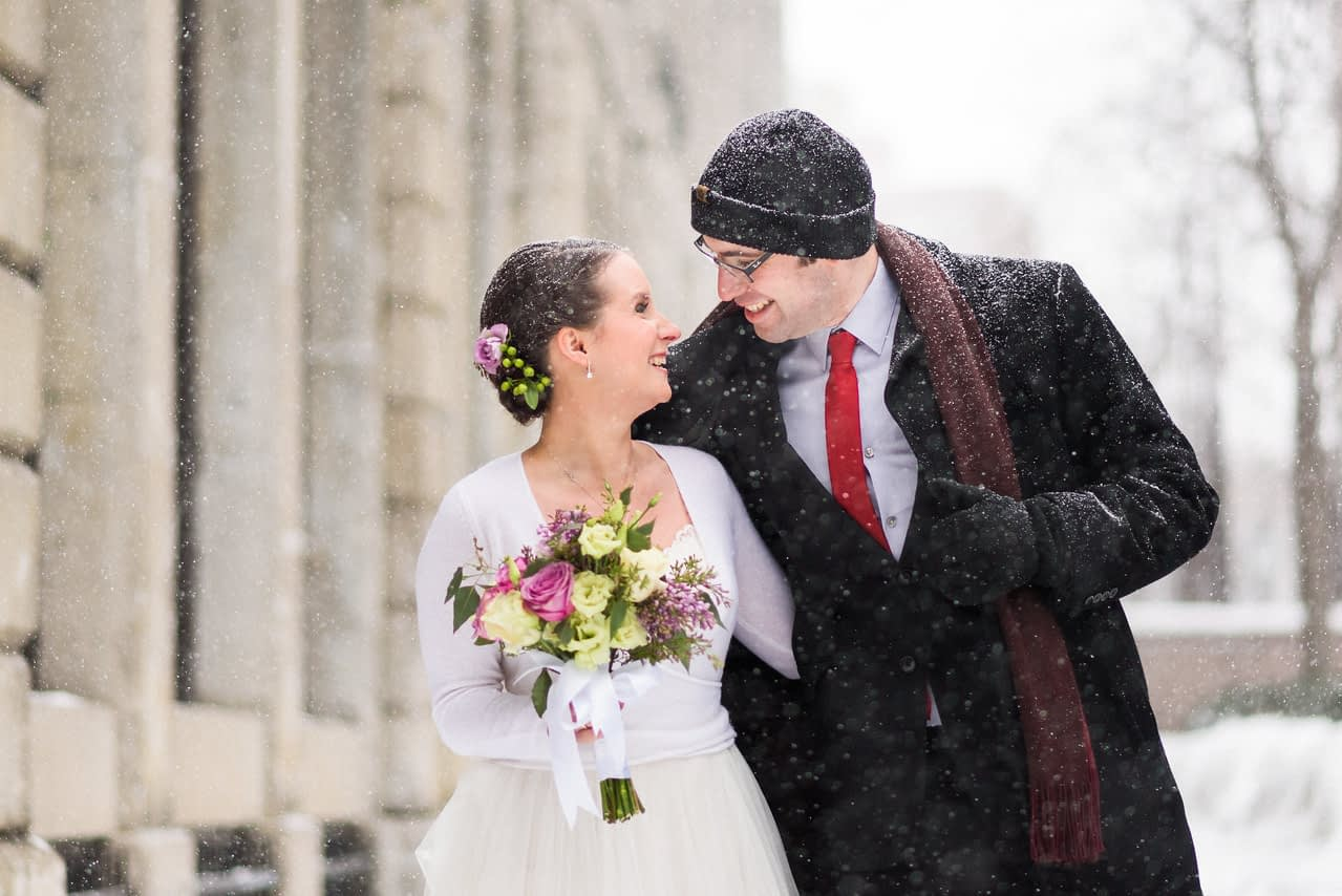 Groom holding his coat open to warm bride during winter photo