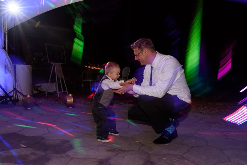 Man dancing with his child at wedding
