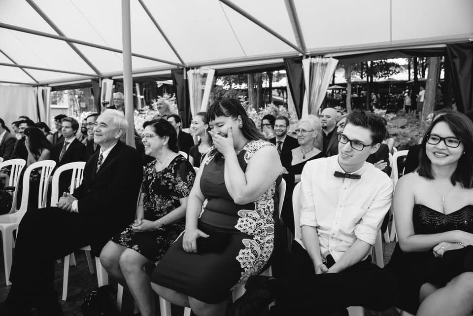 Guests laughing at wedding under tent