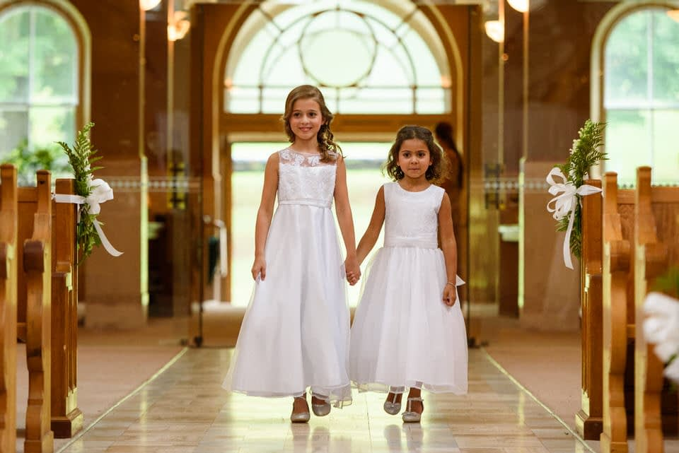 Bride and groom's daughters walking down the aisle at Abbaye d'Oka wedding