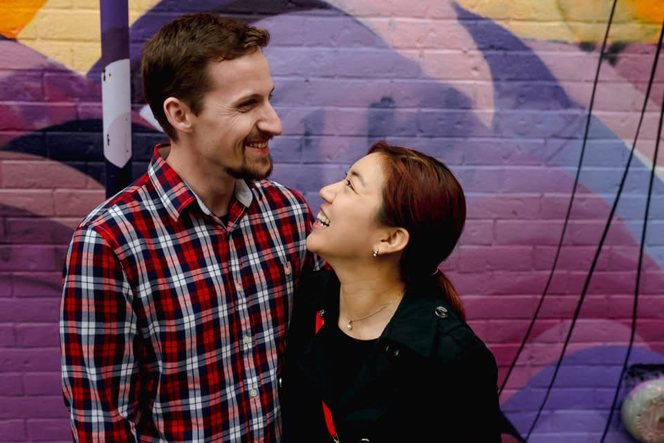 Documentary couple photos near mural in Mile-End Montreal