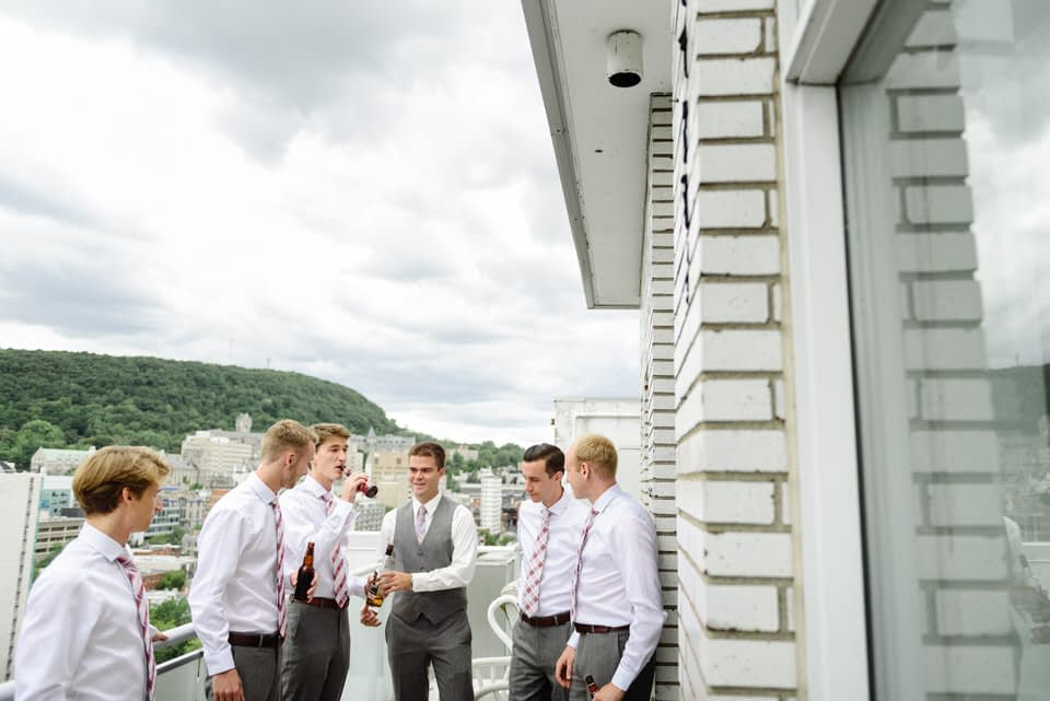 Groomsmen hanging out on the balcony with beers before wedding