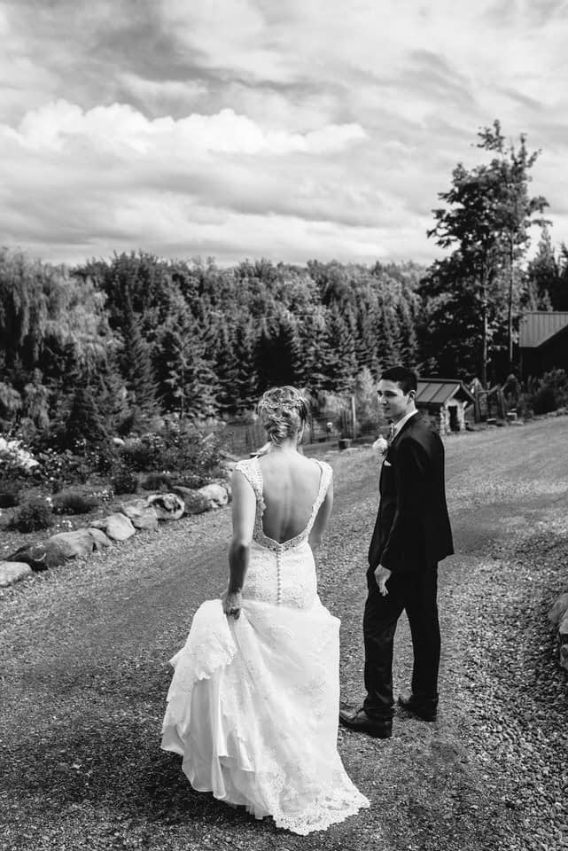 Bride and groom walking down gravel path in mountains in Eastern Townships