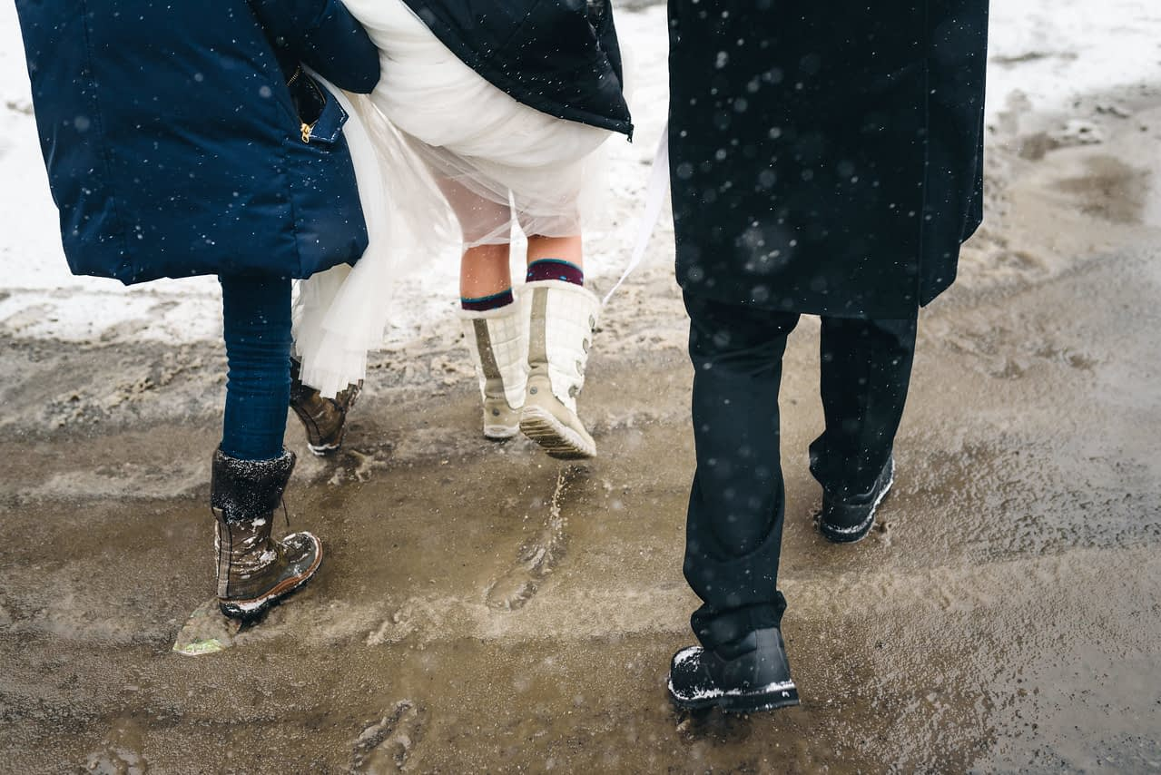 Close up of bride's feet as her friend carries her train
