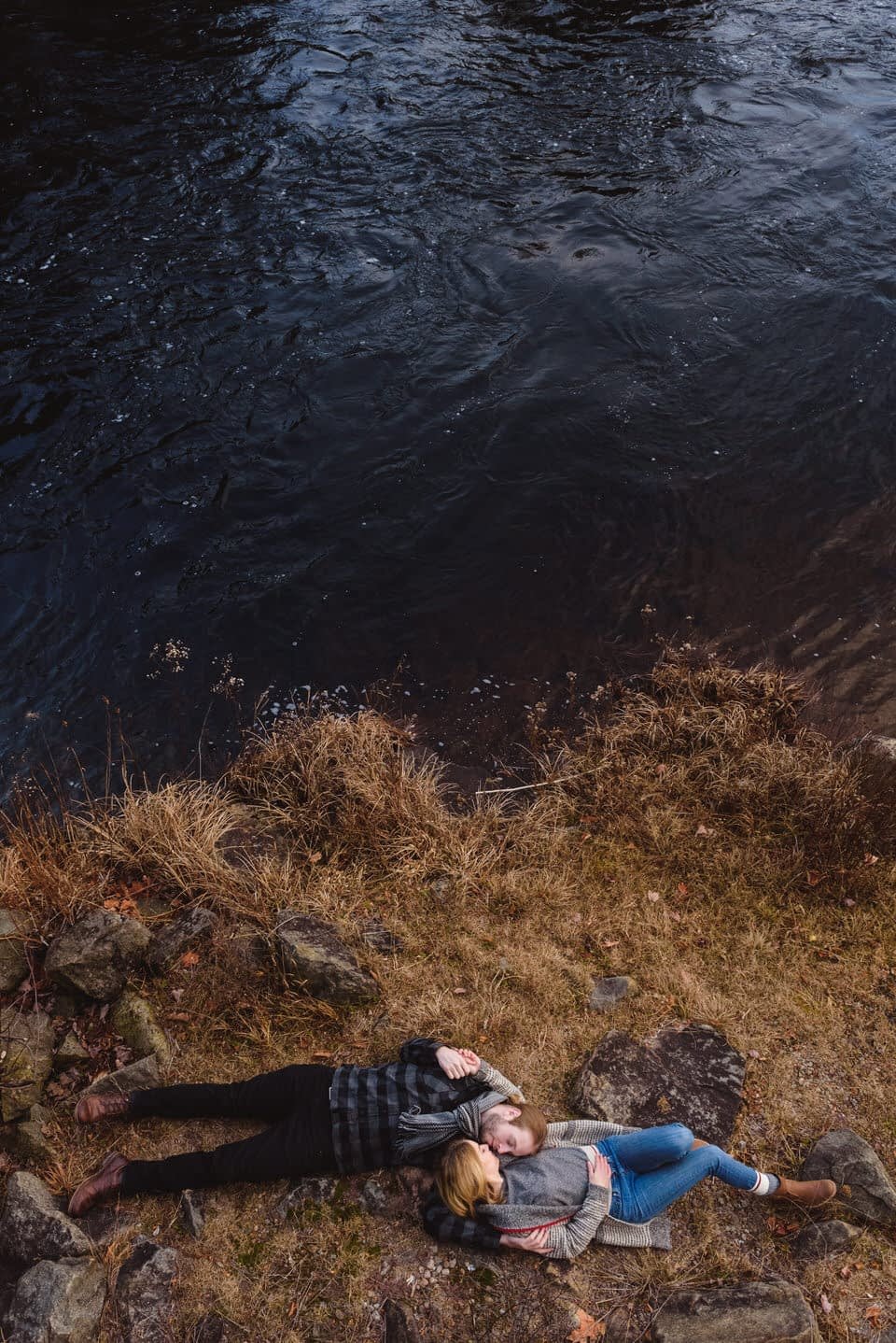 Couple lying down in the brown grass near a dark cold river