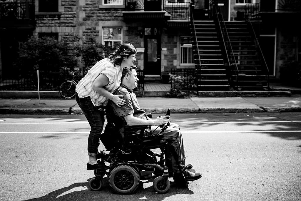 Couple rolling down the street, with woman riding on the back of wheelchair