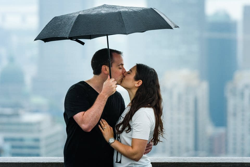 Just engaged couple kissing in the rain