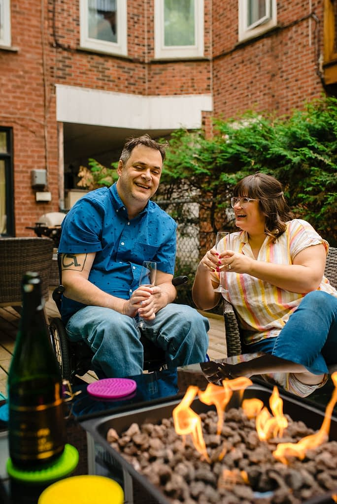 Engagement photo of couple popping champagne in front of a fire pit in backyard