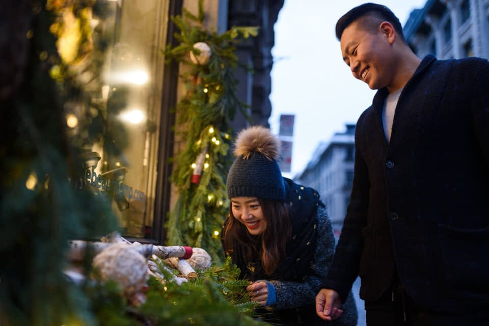 Couple looking at holiday decorations in window in Old Montreal