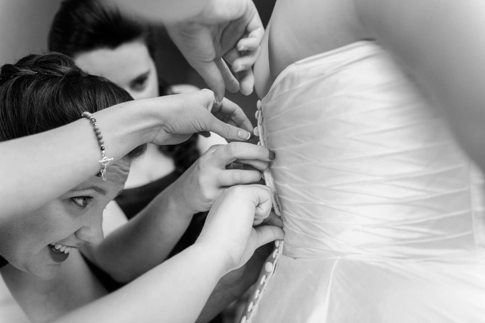 Bridesmaids working together to buttoning up wedding dress