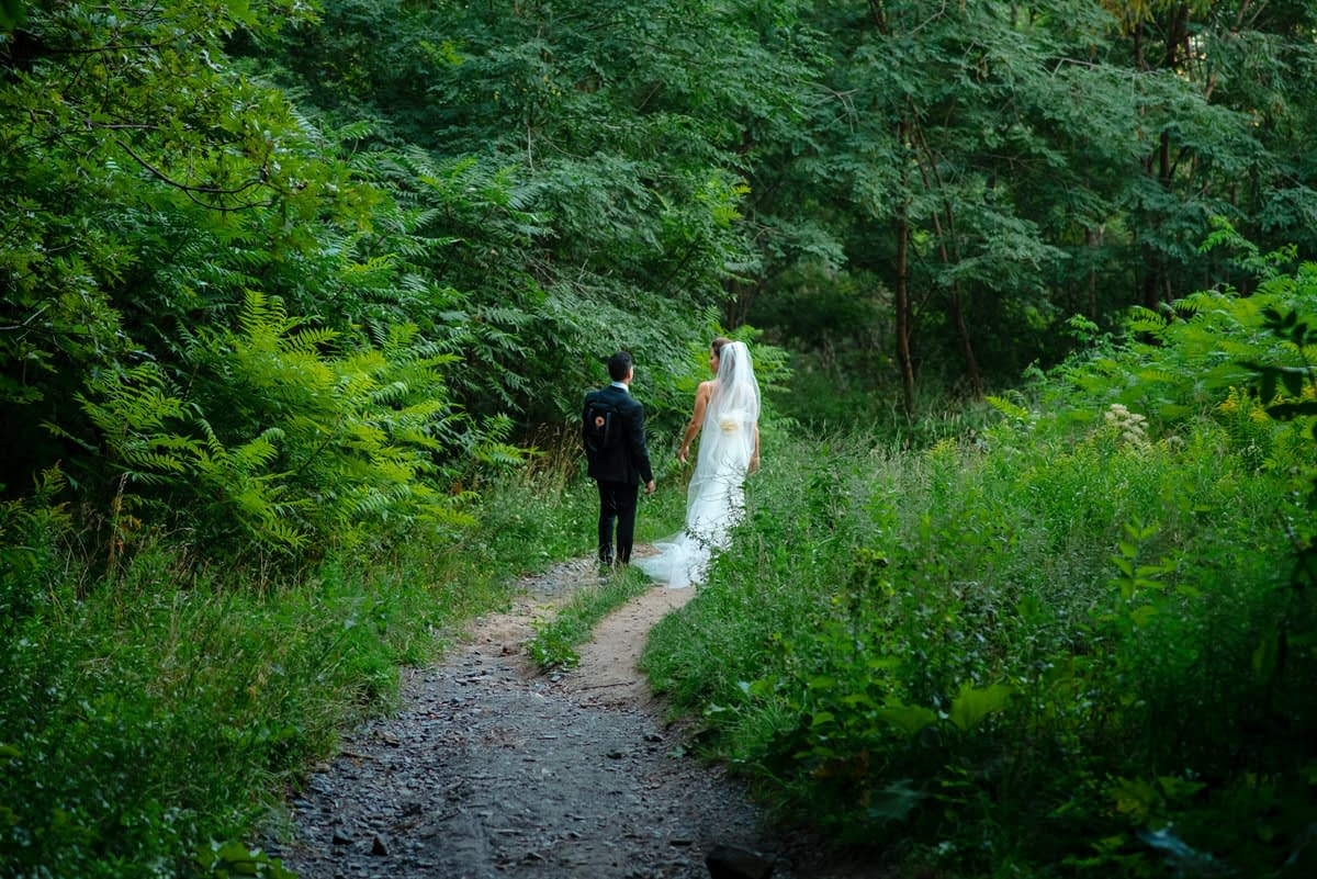 Wedding couple walking in the green woods on Mount Royal
