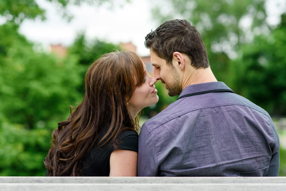 Couple sitting on a bench kissing