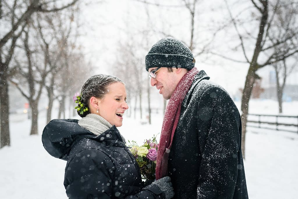 Wedding couple among snowy trees in Old Montreal