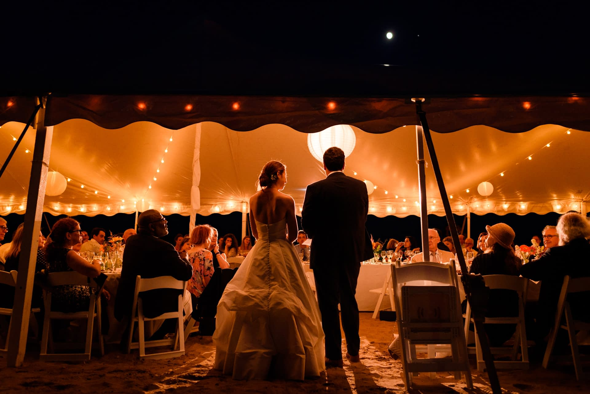 Wedding couple speaking to their guests under the warm glowing lights of a marquee tent on the beach